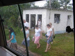 Team members coming out of a house on their prayer walk as it started to rain again.